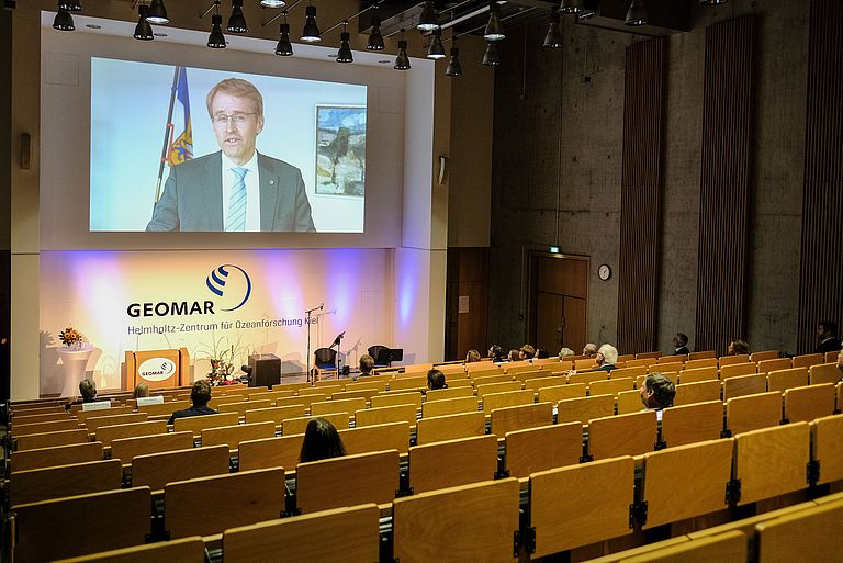 View of the lecture hall with a video message by Minister President Daniel Günther