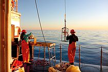 A man and a woman in working clothes stand on the deck of the research vessel ALKOR at dusk. Photo: Jan Dierking/GEOMAR