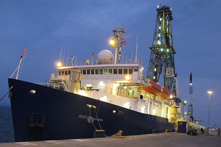 The scientific drilling vessel JOIDES RESOLUTION moored at a pier.