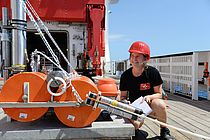 Woman with red hard hat and clipboard in hand squats on a ship deck in front of a device.