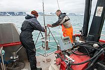 A man and a woman in work clothes stand at the stern of a ship and hold a scientific instrument in their hands. Glaciers can be seen in the background.  Photo: Bo Barker Jørgensen