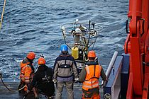 Four crew members of Maria S. Merian secure the PAP buoy to the stern crane.